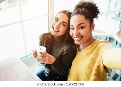 This is a selfie of two beautiful girls that look so amazing and happy at the same time. They are in cafe drinking some coffee end enjoying time spending together. Close up. Cut view.