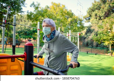 This senior adult woman in a medical mask starts exercising on an air swinger outdoor machine in a city park. She is confident it can benefit elderly people during the pandemic.