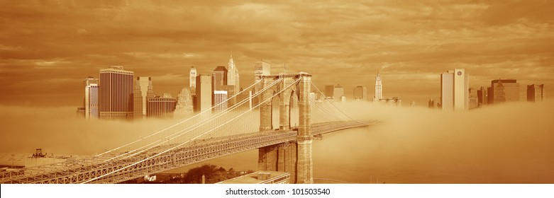 This is a sepiatone of the Brooklyn Bridge over the East River with the Manhattan skyline behind it. There is a morning fog enveloping the bridge.