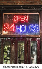 This shop is open 24 hours. Made of red and blue neon tubes. Set on a wood door retro.