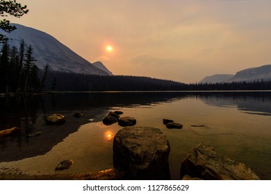 This shot was taken at Mirror Lake in the Uintah Wasatch Cache National Forest. Smoke and falling ash from a nearby wildfire provided such an orange and ominous hue. Truly incredible to see.