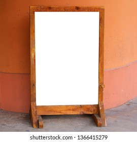This is a sidewalk sign with a wood frame and has a white space for your copy.  It is sitting in front of a building that has a southwest desert looking theme.