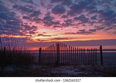 This is a silhouette of a fence in a sand dune at sunrise used to help protect the sand dunes on the Outer Banks of North Carolina.