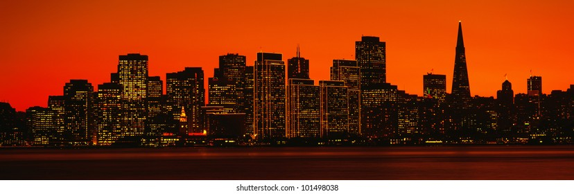 This is the skyline of San Francisco at sunset. There is an orange glow in the sky.