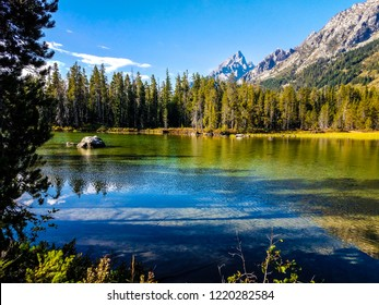 This is a small inlet of Leigh Lake in Grand Teton NP in Wyoming.The reflections of sky, mountains, clouds, and forests are striking and so colorful. A lone boulder sits in the middle of the lake.