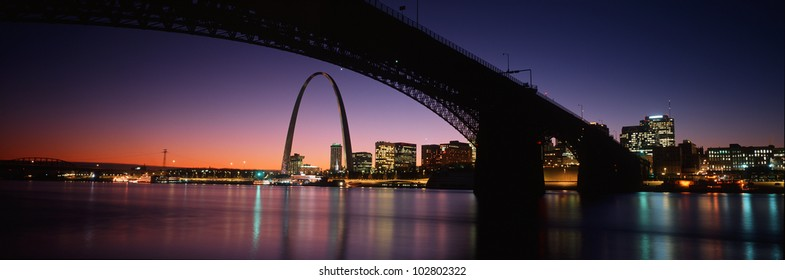 This is the St. Louis skyline and Arch at sunset. Above it is the Eads Bridge along the Mississippi River. There is a purple cast in the sunset sky.