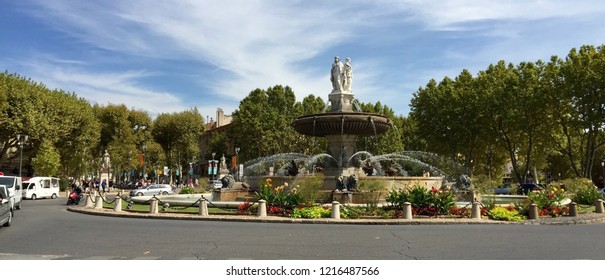 This stately roundabout in Aix en Provence features a fountain and vibrant garden of flowers and shrubs.