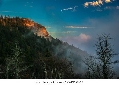 This steep Smoky Mountain, North Carolina cliff has been lit up by the last  rays of sun for the day. Low, colorful clouds have settled over the trees on the cliff, before evening arrives.