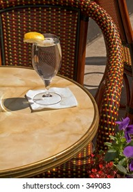 This is a still life photo of a glass of water at an outdoor cafe'.
