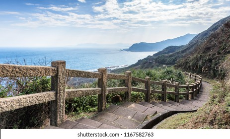 This stunning view was taken in a popular hiking track in Taiwan. The stairs lead downhills along the edge of the cliff. The scenery has mountains and ocean. Steep drop provide exciting to visitors.