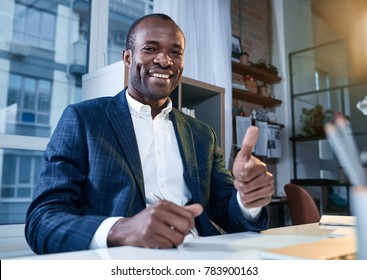 This is success. Low angle portrait of optimistic young confident african man is sitting at table with smile. He is looking at camera with joy and showing thumbs up gesture. Focus on face