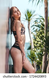 This summer. Young beautiful model with dark hair in stylish swimwear looking at camera while posing outdoors. Tropical nature, summer, relax, resort concept. Vertical shot
