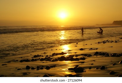This is a sunset from a beach in California with some boogie boarders.