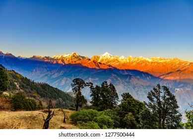 This is the sunset view of Himalayas Panchchuli peaks & alpine landscape from Khalia top trek trail at Munsiyari. Khalia top is at an altitude of 3500m himalayan region of Kumaon, Uttarakhand, India.