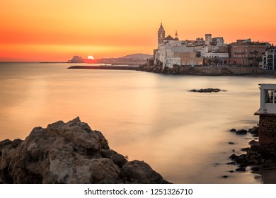 This is a sunset view with rocks on the foreground, the mediterranean sea blurried by a slow shutter speed and the town of sitges in the background.