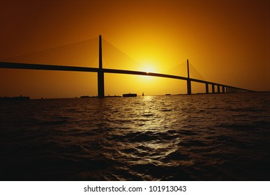 This is the Sunshine Bridge. It is one of the longest suspension bridges in North America. The ocean is shown in the foreground with the bridge in the distance.