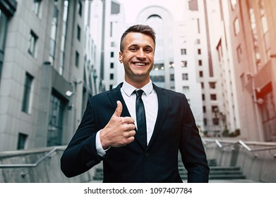 This is a super decision. Beautiful smiling and successful business man in a fashionable black suit looks at the camera and showing thumb up on the background of the metropolis.