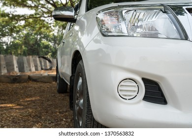 this SUV car is standing under the trees on a sand parking lot