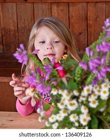This sweet 4 year old girl is behind a cut flower bouquet, arranging the flowers.  Flowers are intentionally blurred to emphasize the child.