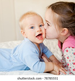 This is a sweet moment between a big sister and her baby brother.  The baby is looking at the camera with a look of delight.  The sister is kissing his cheek.