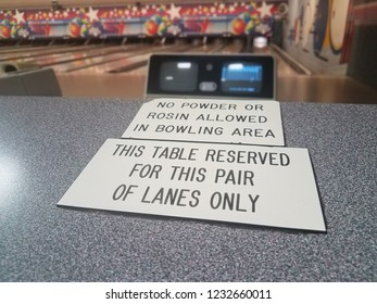 this table reserved and no powder or rosin allowed signs in bowling alley