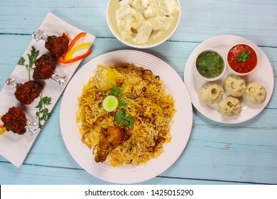 this is table top view of foods containing chicken biriyani in down, paneer butter masala on top, chicken lollipop on right and chicken momo on left.