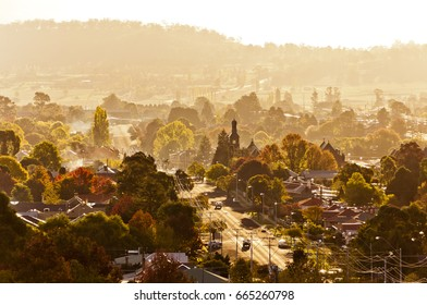 This is the town of Glen Innes in New South Wales, Australia. Morning mist fills a town full of trees in autumn colors.