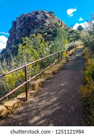 This trail and railing leads to the top of the Thumb Butte Trail in Prescott National Forest in Prescott, AZ. It is a very steep ascent.The Thumb Butte is seen up the trail on the left.