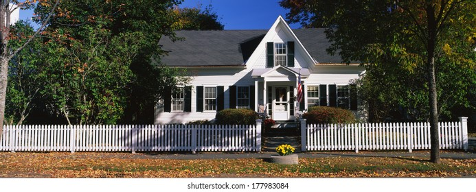 This is a typical suburban single-family home. It is a white house with a picket fence in front. This typifies the American dream for most people, New England.