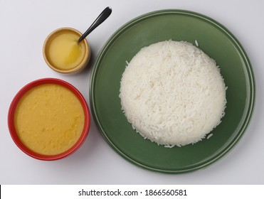 This is a very commonly consumed dish called Dal Chaval or Dal Rice, the rice served in a green plate and the Dal is served in red bowl with Ghee and all this is placed on a white background.
