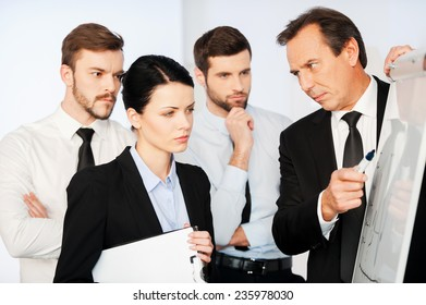 This is very important! Confident mature businessman pointing a graph on whiteboard while his colleagues standing near him and looking at sketch