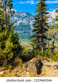 This is a view of Jenny Lake, mountains in the distance, and a tour boat doing its crossing. Jenny Lake is located in Grand Teton National Park in Wyoming.