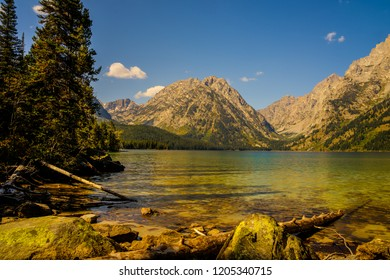 This is a view of Leigh Lake from the Leigh Lake trail in the Grand Teton NP in Wyo.The calm lake reveals subtle reflections of the background mountains. Fallen trees have collected at the shoreline.