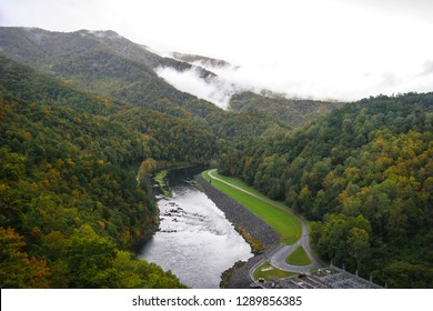 This is a view from near the Fontana Dam, 480 feet in height, near Bryson City, NC. The clouds are touching the mountains in background, and the Autumn color tinged Nahantala NF, surrounds the gorge.