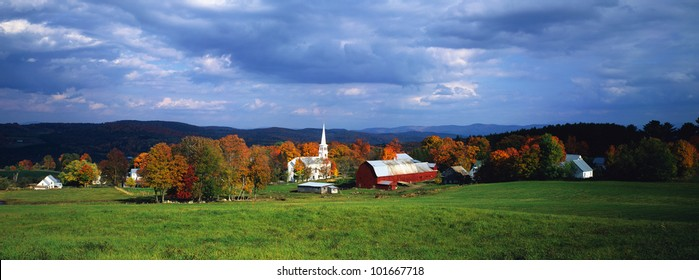 This is a view of a village in autumn. There is a typical New England white church with a tall steeple and a red barn.