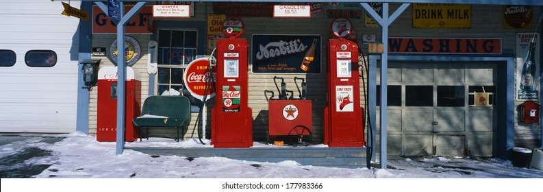 This is a vintage gas station with old style pumps that are red. It is a piece of Americana. It shows winter in New England.