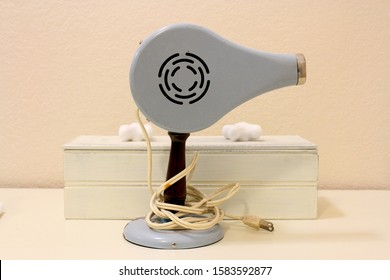 This is a vintage retro looking blue hair dryer from the 1950`s.  It has an electric cord and is sitting in front of a box and a pink wall.