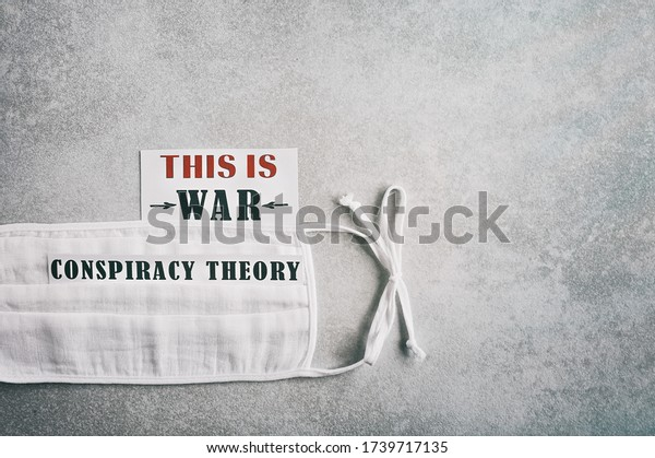 """""""This is war. Conspiracy theory."""" Text on a sheet of paper and a light gray background. Beware of scam related to Coronavirus Covid-19."""