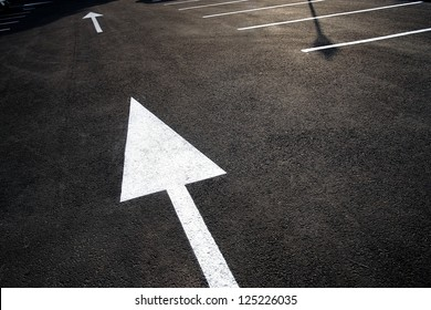 This Way: strong directional / pointing white arrow / roadsign painted on black asphalt. Leadership strategy execution concept. Strategic planning, solution / decision, action plan, guide. Copy space.