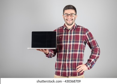 This is what you need! Confident young man carrying laptop and showing screen of it standing against gray background