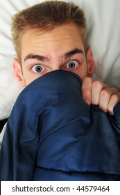This white Caucasian young adult teenage man hides under his blankets and covers because he is scared of the spooky things that go bump in the night.