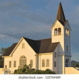 This white church is a historic landmark in Conway, Washington on Fir Island.  Sunset is hitting against a darker sky background.