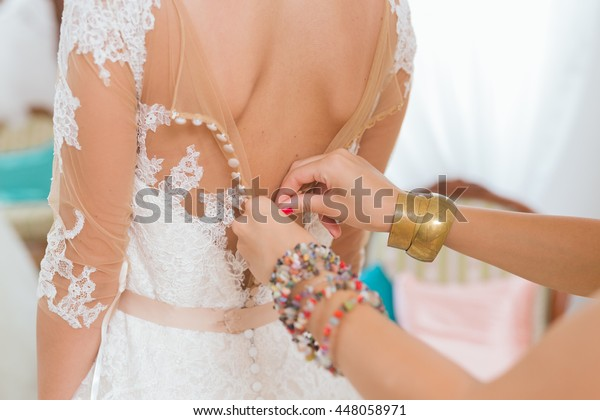 This will be a perfect dress. Helping the bride to put her wedding dress on