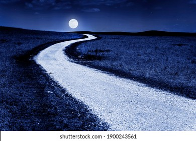 This winding country road in the Tallgrass Prairie of Kansas glows in the moonlight of a full moon, a photo illustration that makes you feel like you can drive to the moon.