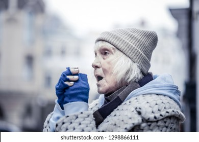 This is winter. Depressed aged woman suffering from cold temperature while being outside