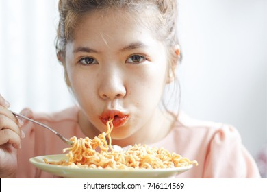 This woman is eating spicy Korean instant noodle by using forks. White background. green plate. Chili hot.