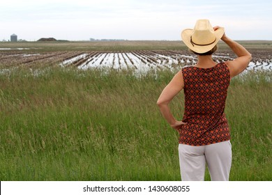 This woman is standing with her hand on her cowboy hat while looking towards a wet farm field.  The farm field rows in the distance are covered with water.