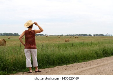 This woman wearing a cowboy hat is standing on the side of a rural country road looking at a field of hay bales.  The hay bales are rolled in circles in the farm field off in the distance.