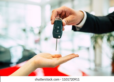 This is a wonderful choice. The woman's hand receives the keys from the new car from the salesman in the dealership.