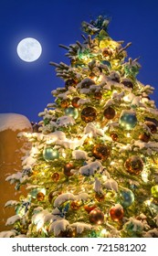 This wonderfully decorated Christmas Tree in Santa Fe New Mexico glows brightly at night as a light snow falls. The full moon adds the final decoration along side the snow covered adobe wall.